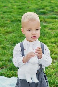 Счастливого пасхального кролика. ребенок с удовольствием на открытом воздухе. оягнитесь играть с яичками и кроликом на зеленой траве.