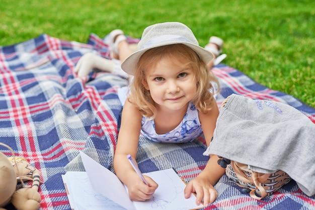 ピクニックに公園で本を持つ少女