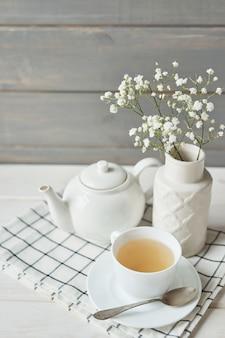 Красивый яркий чайный сервиз. белые керамические чайники и чайные ингредиенты, сверху белого стола.