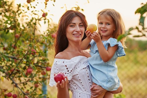 Счастливая семья, сбор яблок на сад. мать и дочь в яблоневом саду