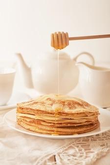 パンケーキウィーク:テーブルの上に蜂蜜と紅茶のパンケーキ