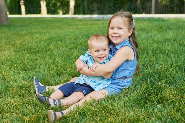 草の上の公園で彼女の兄弟を持つ少女