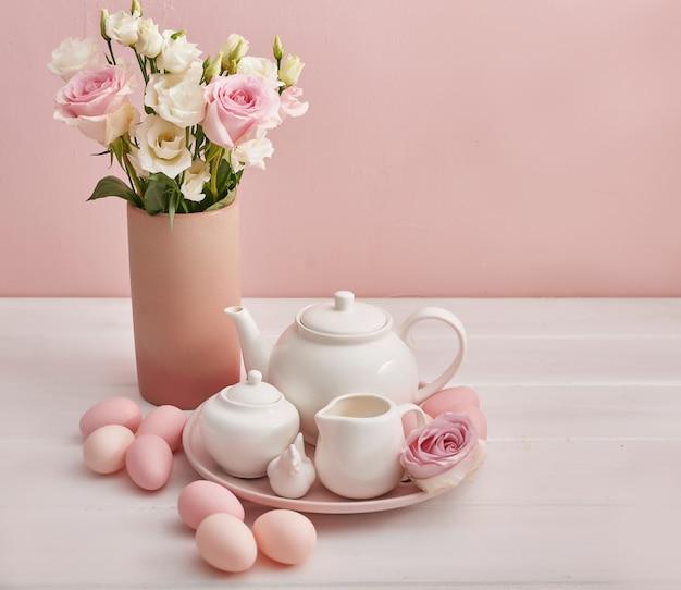 Пасхальный чайный сервиз и красочные яйца на праздничном столе.