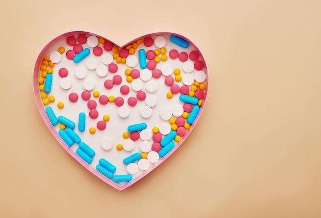 各種医薬品の丸薬、錠剤、カプセルベージュ色の背景に。医学の概念と健康