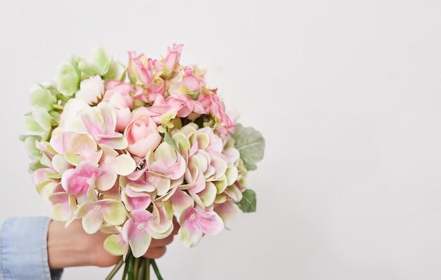 花の背景の花束を持つ子少年。母の日。
