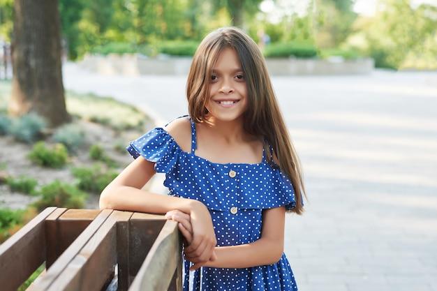 青いドレスのティーンエイジャーの女の子が日没で夏の公園で歩く