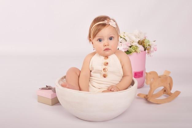 Милый забавный ребенок с цветами и игрушкой. милая девочка