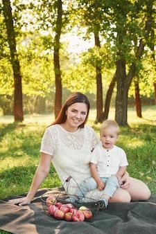 母と息子は日没で夏に公園を散歩します