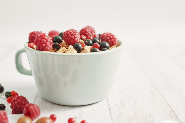 Красочные свежие ягоды с хлопьями в белой чашке