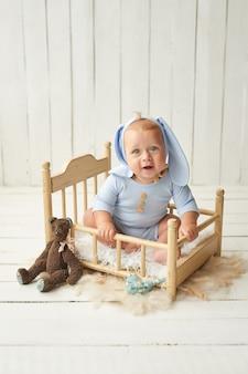 Пасха мальчик сидит на кроватке. пасхальный заяц. счастливый ребенок
