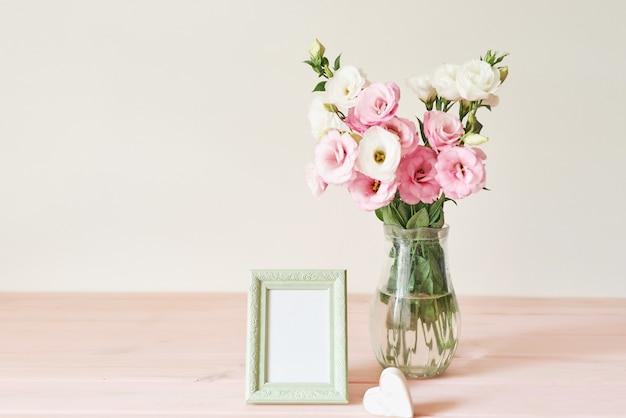 フォトフレームとテーブルの上の花瓶の花