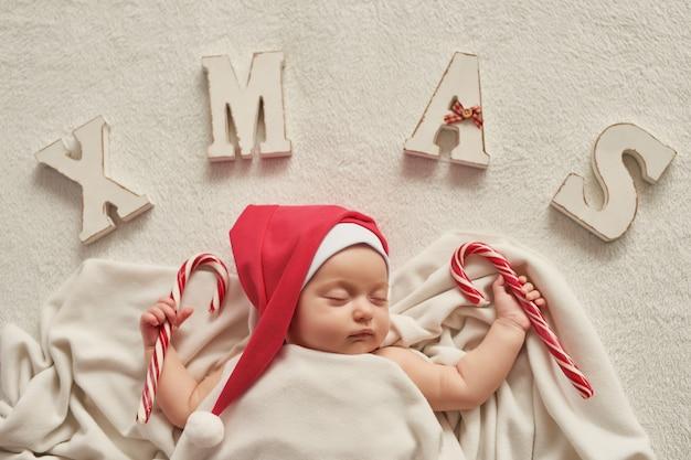 Санта малыш с новогодним украшением на свету