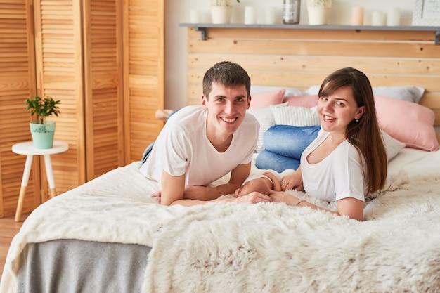 Фамильные молодые родители с новорожденным ребенком дома на кровати
