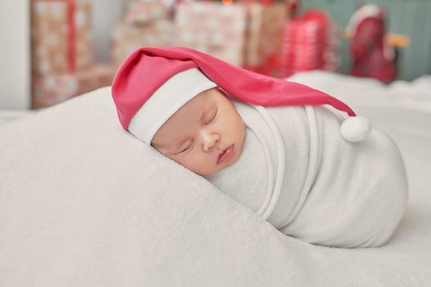 明るい背景に新生児の女の子サンタ