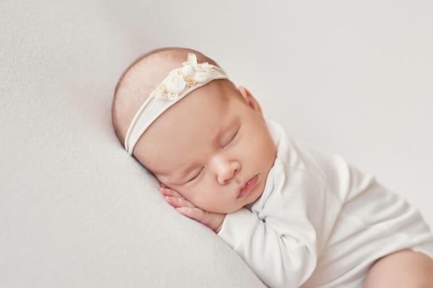 Новорожденная девочка на светлом фоне