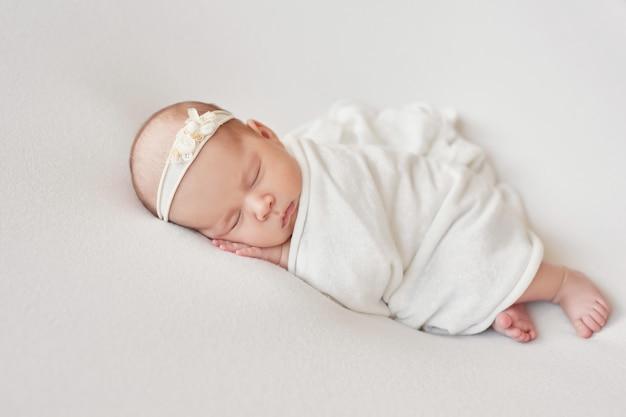 明るい背景に生まれたばかりの赤ちゃんの女の子