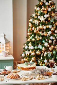 テーブルの上のクリスマスのお菓子:カップケーキ、裸のケーキ、クッキー、コーヒーと蜂蜜
