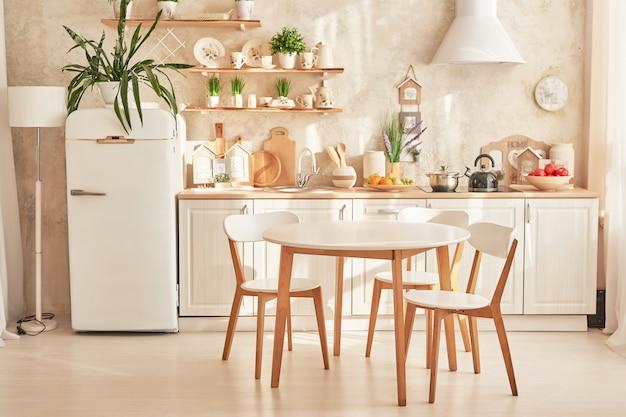 ダイニングテーブルと白いスカンジナビアスタイルのキッチン