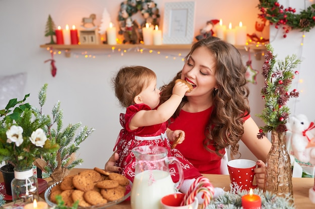 クリスマスに飾られた台所で赤ちゃんを持つ女性。