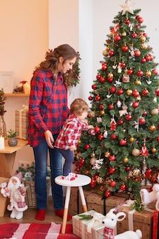 Мама с ребенком на кухне украшены на рождество.