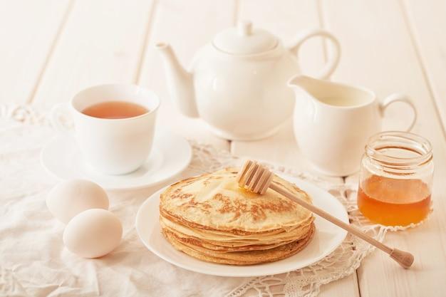 パンケーキウィーク:テーブルに蜂蜜と紅茶を添えたパンケーキ