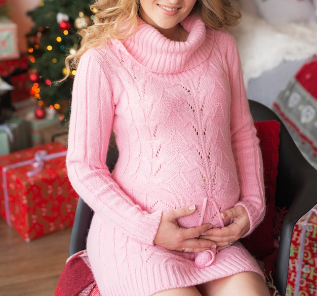 Беременная девушка в канун рождества дома возле новогодней елки