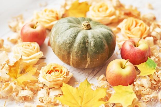 リンゴ、花、葉と秋の背景にカボチャ。