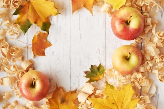 葉、リンゴ、花の秋の背景。