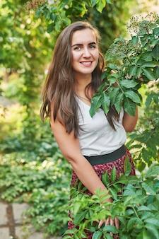 緑の近くの夏の公園で笑っている女の子