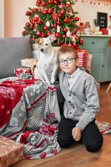 クリスマスの背景にクリスマスツリーの近くに犬を持つ少年