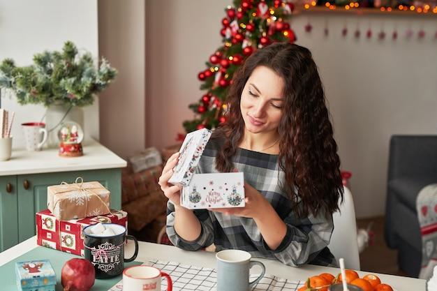クリスマスキッチンで贈り物を持つ少女