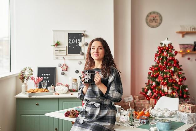 Девушка с чашкой в новогодней кухне
