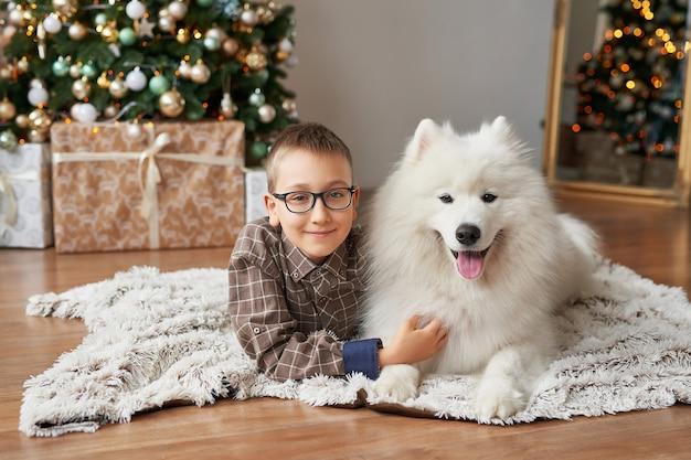クリスマスシーンにクリスマスツリーの近くに犬を持つ少年