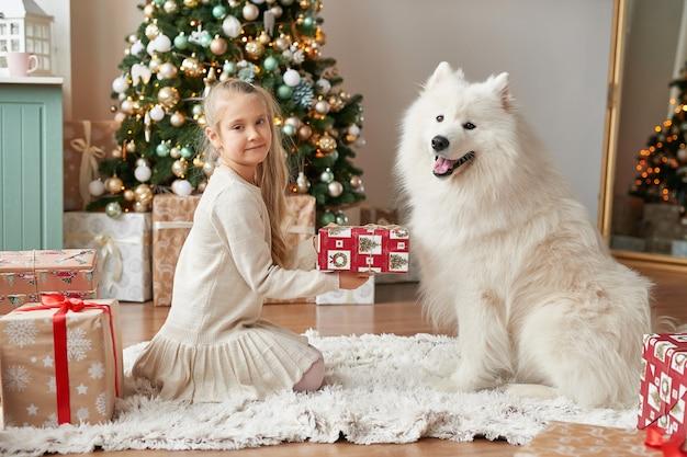 クリスマスシーンにクリスマスツリーの近くに犬と少女