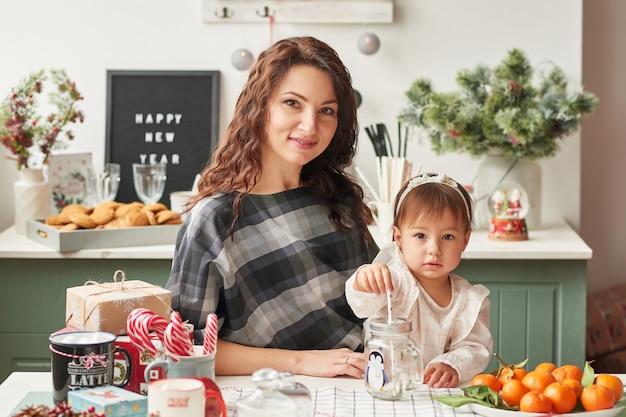お母さんと台所で小さな娘が新年とクリスマスの装飾