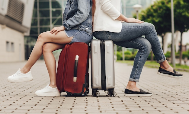 Две женщины сидят на чемоданах в ожидании рейса. закройте вверх милых женских ног в джинсах и юбках на серых и красных чемоданах. путешествуйте с друзьями. туристы ждут поездки