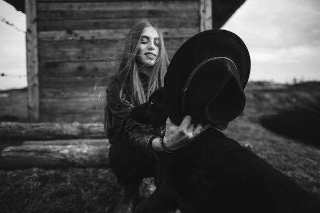 彼女の黒い犬と遊んで幸せな若い女