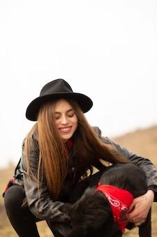 黒い帽子を持つ幸せな若い女