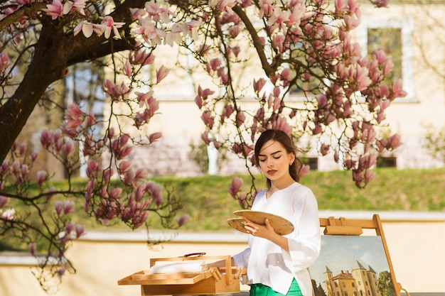 ブラシとパレットを手で保持している若いブルネットの女性アーティスト。