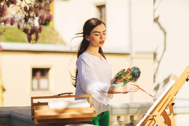 若い笑顔ブルネットの女性アーティストは路上で絵を描く