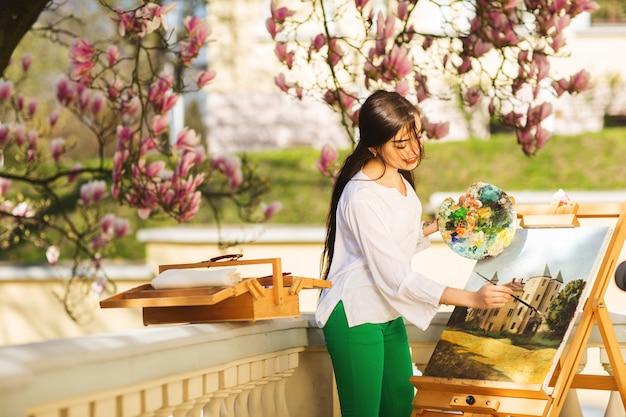 若い笑顔ブルネットの女性アーティストは、モクレンの美しい木の近くの通りに絵を描く
