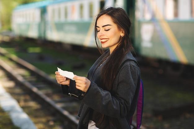 電車の近くのバックパックを持つ女性は駅のプラットホームへの彼のチケットをチェックします。