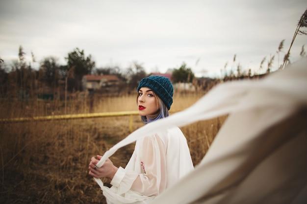 スタイリッシュな帽子と麦畑を歩いて白いドレスの少女
