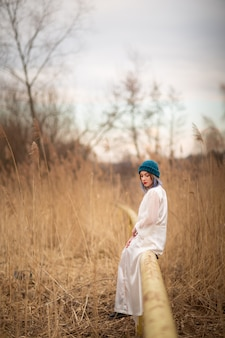 麦畑の近く、パイプの上に座って、白いロングドレスを着た少女