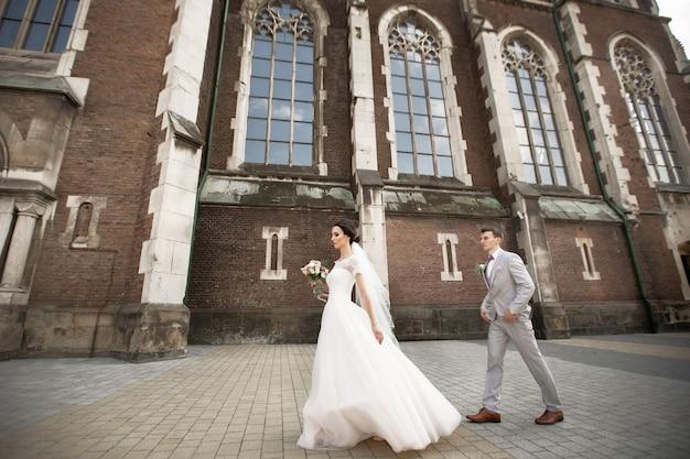 美しい新婚カップルは、古いキリスト教の教会の近くを歩きます