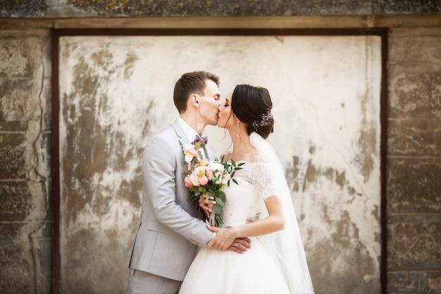 美しい結婚式のカップルが古い壁の近くにキス