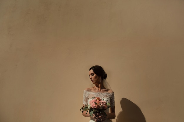 壁の背景に花の束を持つ花嫁の肖像画