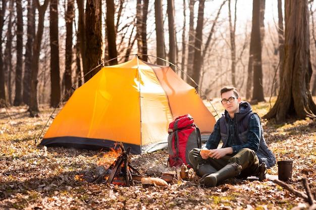 森の中の若い旅行者は自然の中でテントと調理された朝食の近くで休んでいます