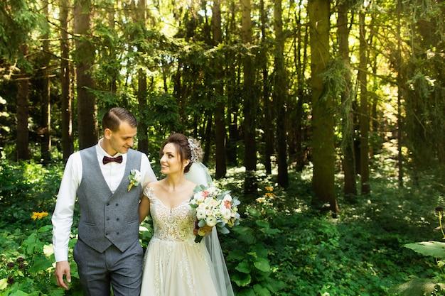 結婚式のカップルは森の中を歩いて楽しんでいます。新婚夫婦は抱擁し、手を握る