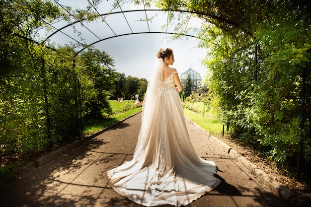 自然の背景にファッションのウェディングドレスの花嫁。公園の美しい女性の肖像画。背面図